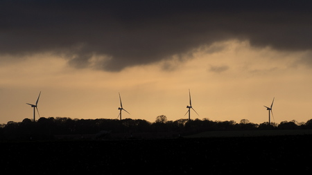 Wind turbines on a hillside silhouetted against a stormy and overcast evening sky at sunset