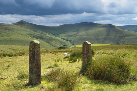 View over sunlit mountains in the Peak District National Park with old rock gate posts in the foreground and dark clouds overhead, UK Archivio Fotografico