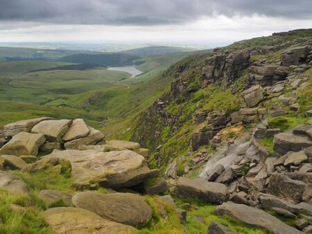 Kinder Downfall overlooking Kinder Reservoir with the wind blowing the waterfall back into the air against dark storm clouds overhead, Peak District National Park, UK Banco de Imagens