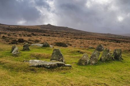 Nine Maidens Bronze Age megalithic cairn circle under Belstone Tor with dark brooding stormy sky, Dartmoor National Park, Devon, UK