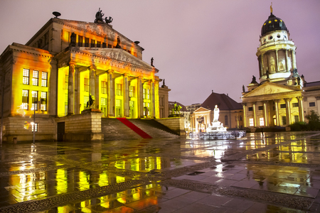 Panoramic view of famous Gendarmenmarkt square with illuminated Berlin Concert Hall and French Cathedral reflecting on wet floor after rain in twilight during sunset in Berlin city center 新聞圖片