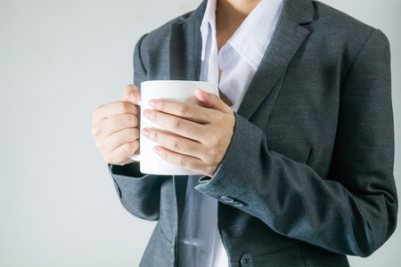 black suit bussiness women holding a cup of coffee in break time