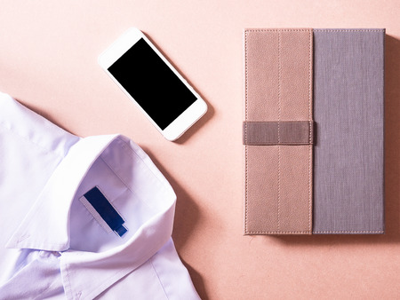 new employees: business clothes set of white smart phone and notebook in concept new employees