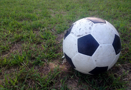 soccer goal: old ball on the green grass