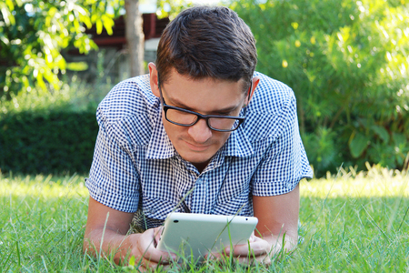 beau jeune homme: Handsome young man looking at the tablet wearing glasses and checkered shirt lying on the grass outdoors