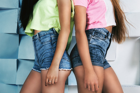 sexy blonde girl: Two young fit girls in high waistline jeans shorts and bright colored t-shirts