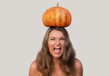 screaming girl: Attractive screaming girl with halloween pumpkin on her head on white background