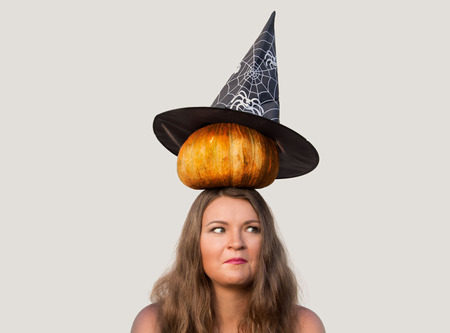 role models: Confused beautiful girl with pumpkin on her head and halloween witch hat on white background