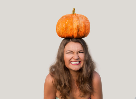 giggling: Giggling beautiful girl with halloween pumpkin on her head on white background