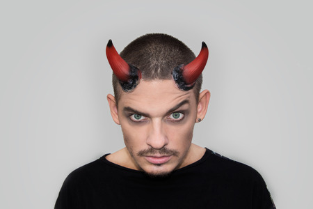 young boys: Andry man with halloween horns staring at the camera on white background Stock Photo
