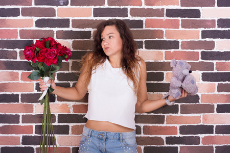 deciding: Young beautiful girl holding bouquet of roses and teddy bear in her hands and deciding what to choose Stock Photo