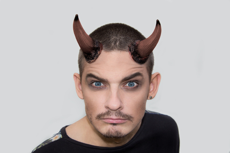 horns: Angry young man with halloween horns on white background Stock Photo