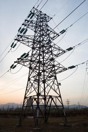 over voltage: High voltage electricity pylon over sunset.