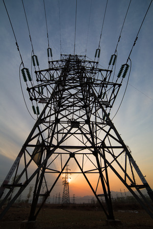 High voltage electricity pylon over sunset. photo