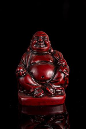 Smiling buddha budai statue over black photo