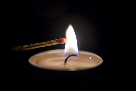 ignited: Candle ignited a match on black ground