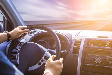 hombre conduciendo: Las manos de un conductor en el volante de un coche y la carretera de asfalto vacío Foto de archivo