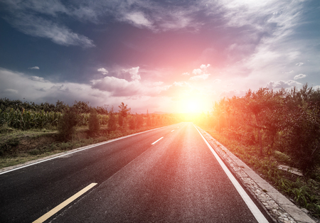 road vehicle: asphalt road through the green field and clouds on blue sky in summer day Stock Photo