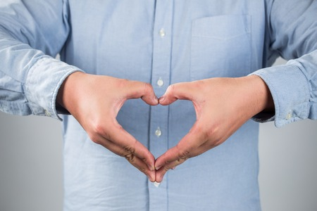 care: Closeup portrait handsome smiling young business man makes the heart using fingers, hands, isolated grey wall background. Positive human emotions, facial expressions, feelings, body language, attitude