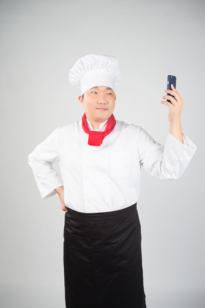 red scarf: Young Cook With Red Scarf Looking At Phone Surprised Stock Photo