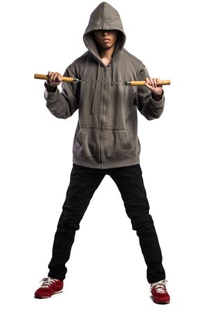 nunchaku: asian man in a hood is using a nunchaku Stock Photo