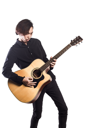 music player: Young man playing guitar on white background looking to the camera Stock Photo