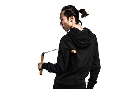nunchaku: asian man in a hood is using a nunchaku isolated on white