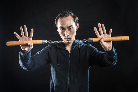 nunchaku: asian man in a hood is using a nunchaku isolated on black Stock Photo