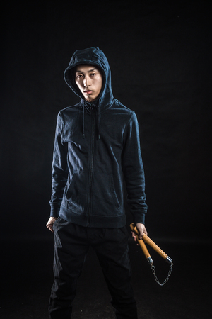 asian bodybuilder: asian man in a hood is using a nunchaku isolated on black Stock Photo