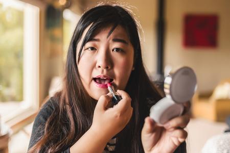 woman mirror: Young woman making make-up near mirror