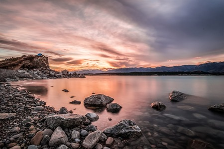 cloud capped: Sunset at Mount Cook National Park alongside Lake Pukaki with snow capped Southern Alps basking in the late winter afternoons golden light. The setting sun cast vivid pastel  hues on the sky. Stock Photo