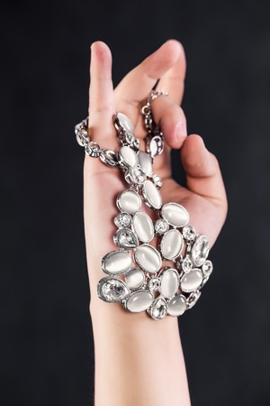 carbuncle: necklace in right hand isolated on grey Stock Photo