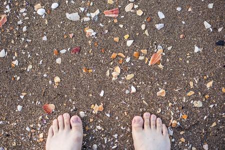 painted toenails: legs on beach. top view nice photo Stock Photo