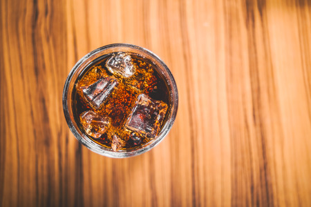 carbonation: soft drink splashing from glass on wood table