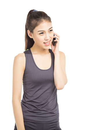 conversaciones: Young smiling fair-haired sportswoman talks by mobile phone against big sports hall.