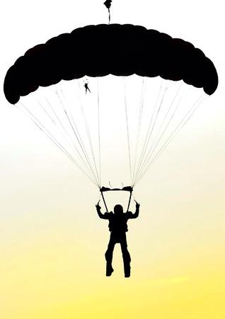 Parachuter busting a jump at dusk.