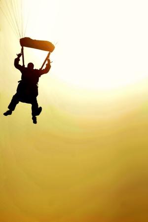 Parachutist jumps at sunset.