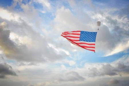 단일 skydiver 미국 국기를 들고 흐린 푸른 하늘에 대 한 이동