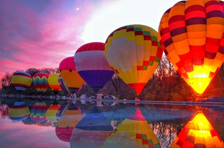 A row of hot air balloons light up next to a reflecting pool at a local festival