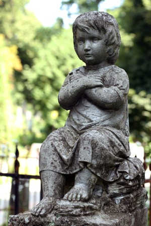 eminence: Old statue boy on grave in the Lychakivskyj cemetery of Lviv, Ukraine.