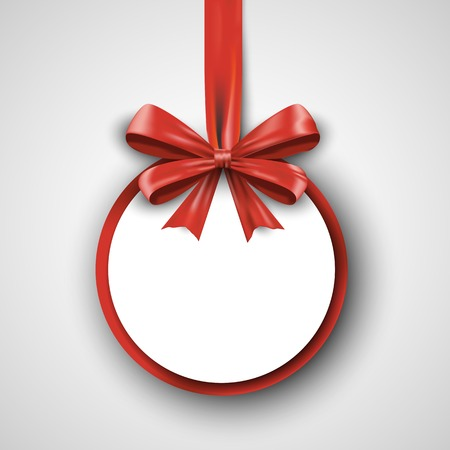 satin round: Christmas round gift card with red ribbon and satin bow. Stock Photo
