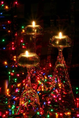 tea light candles atop crystal wine glasses in festive setting