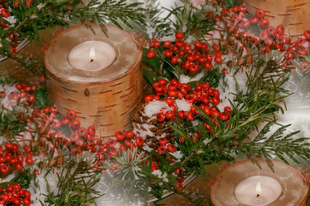 Centrepiece: birch bark candles amidst greens, berries, fake snow Stock Photo