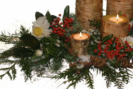 birch bark candles amidst holiday greens, berries, fake snow