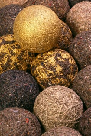daubed: gold-painted cork ball atop yarn balls, some daubed with gold paint