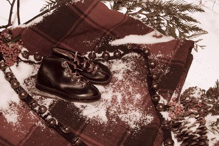 vintage winter holiday concept: old skates, plaid horse blanket, sleigh bells, pine cones, berries & snow