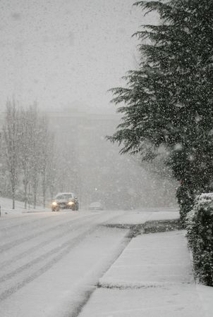 wintry background: huge snowflakes at onset of snowfall with limited visibility for cars Stock Photo