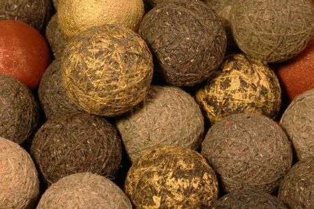 daubed: textile background: yarn balls of different shades & fiber mixes, some with gold paint daubed on them, with two red & one gold painted cork ball.