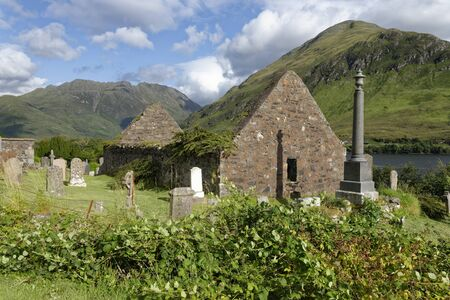 Remains of 15th century St Dubbtbach's Church with Sgurr a' Choire Ghairbh (left) & Sgurr na Moraich (right) behind Loch Duich, Hightland, Scotland, UK