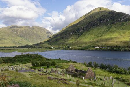 Remains of 15th century St Dubbtbach's Church with Sgurr a' Choire Ghairbh (left) & Sgurr na Moraich (right) behind Loch Duich, Hightland, Scotland, UK